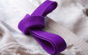 BJJ purple belt atop white gi