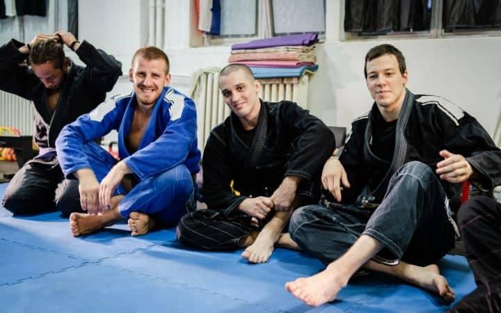 Jiu Jitsu teammates sitting in gymas a reason why Jiu Jitsu is a team sport | Jiu Jitsu Legacy