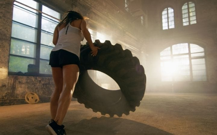 Woman training with a tyre - The Best BJJ Conditioning Tools for Endless Cardio | Jiu Jitsu Legacy