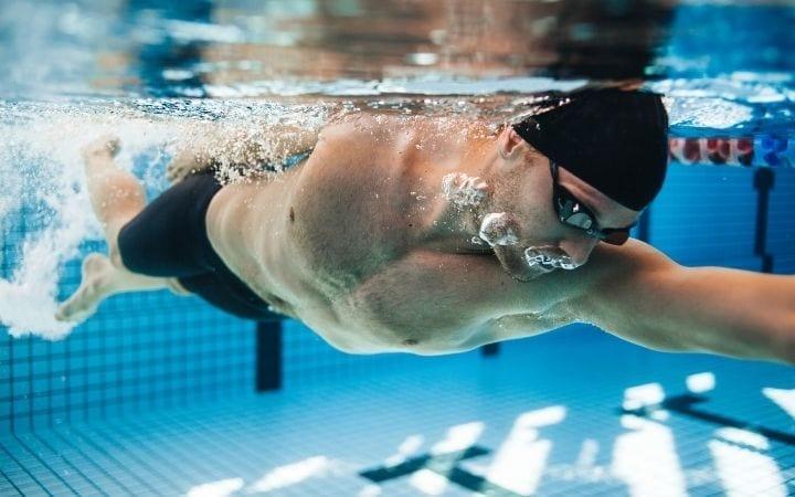 Man swimming in the pool, how swimming helps build endurance for BJJ | Jiu Jitsu Legacy