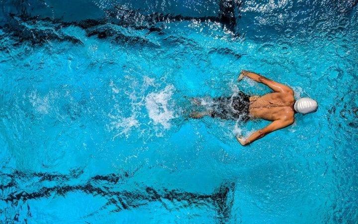 Man swimming in the pool, how can Swimming for BJJ help build endurance | Jiu Jitsu Legacy